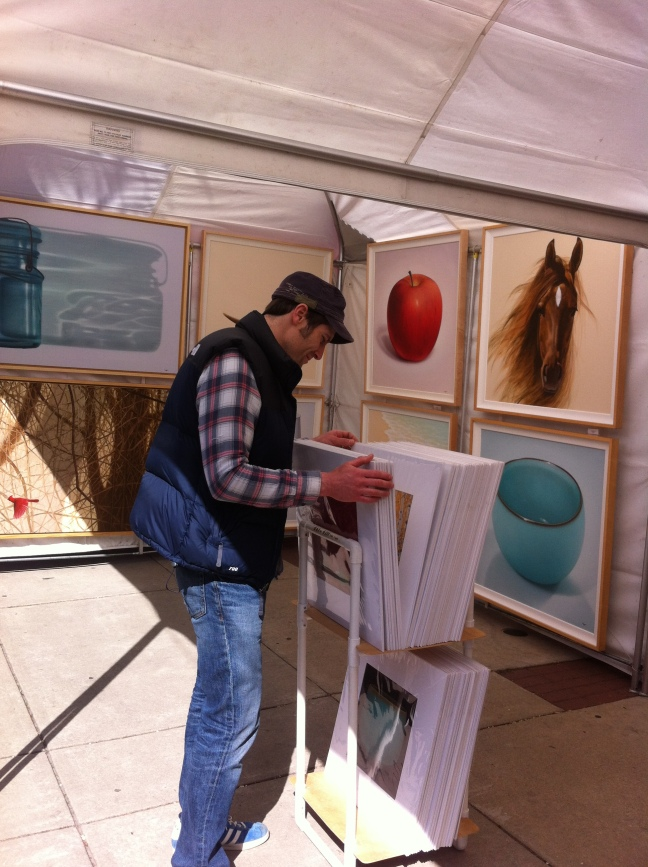 A customer visits the booth of painter, Zu Sheng Yu at Art on the Square 2013.